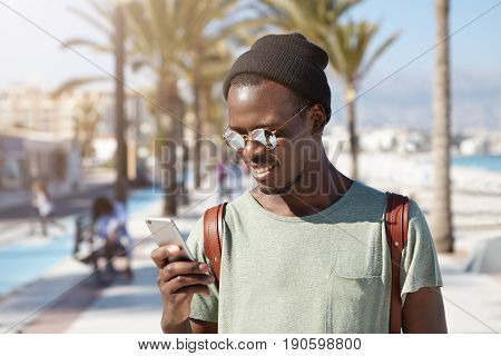 Horizontal Portrait Of Fashionable Black African Male In Summer Shades And Black Hat Travelling In B