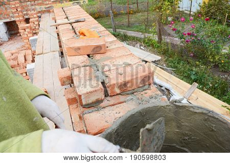 Bricklaying Brickwork. Bricklaying on House Construction Site. Building Home wall. Bricklayer Worker Installing Red Bricks and Caulking Brick Masonry Joints Exterior Wall with Trowel putty Knife