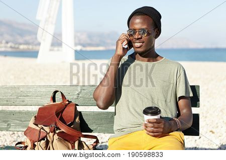 People, Lifestyle, Rest And Technology Concept. Black Male In Trendy Wear Sitting At Bench Against S