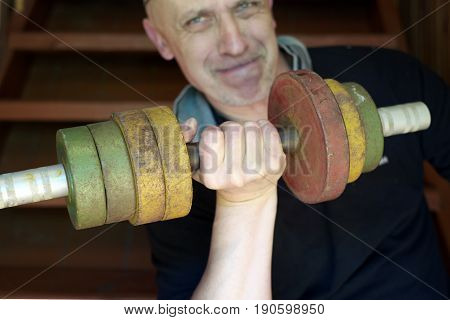 Man with a serious face pumping a dumbbells indoor cropped shot with focus in the foreground