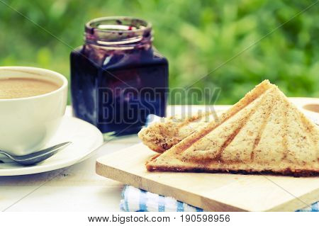 Sandwich with tuna spread and coffee on white wooden table. Selective focus and copy spaceVintage style.