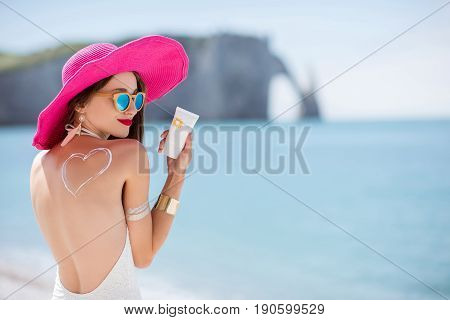 Portrait of a beautiful smiling woman in pink hat with sunscreen heart shape on her shoulder holding a sun cream bottle on the beach