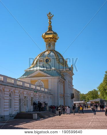 Petergof, Russia - June 5, 2017: The building is a special pantry. The baroque dome is decorated with a double-headed eagle. People go on an excursion.