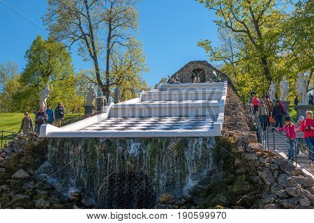 Petergof, Russia - June 5, 2017: Cascade Chess mountain. Left and right are statues of the ancient gods. In the foreground is the entrance to the lower grotto. At the top of the dragon sculpture.