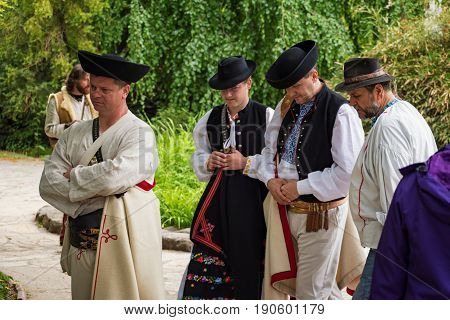 Piestany, Slovakia – May 20 2017: Four Unidentified Men, Dressed In Folk Costumes, Seem To Be Unhapp