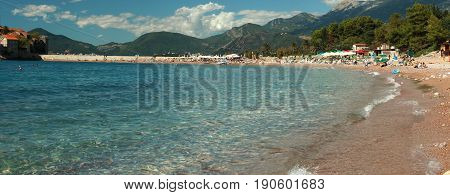 A horizontal panorama overlooking the sea bay with a beach and a lot of people having a rest. Clear clear water, mountains and a cloudy sky in the distance.