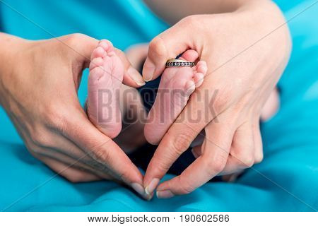 Mother's hands forming a hearth around baby feet. Fanily love.