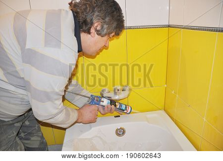 KIEV - UKRAINE JUNE - 19 2017: Bath tube installation with Silicone Bathroom Caulk water tap in the yellow tiled bathroom. Repair bathroom with new bath tube. Silicone a Bath with Caulking Gun
