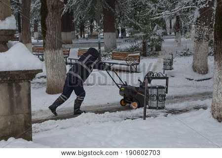 Man using a snow throwing machine on a winter day after a snowstorm dumped 8 inches of snow. Man operating a snow blower. Man removes snow with gas snow thrower at winter day