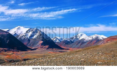 The mountainous landscape. The chain of mountain peaks covered with white snow. At the foot of the barren stone desert. (Mountain Altai)