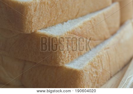Sliced bread stack on wood plate close up concept. Soft and sticky homemade bread for delicious toast in breakfast. Homemade bakery background with copy space in sliced bread concept. Delicious and soft homemade bread stack on wood plate.