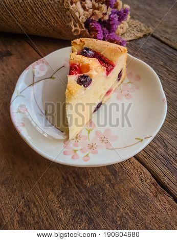 Homemade butter cake with blueberry and strawberry. Triangle slice piece of butter cake on lovely white plate put on rustic wood table. Soft and moist mixed berry butter cake on wood background. Delicious butter cake for coffee break.