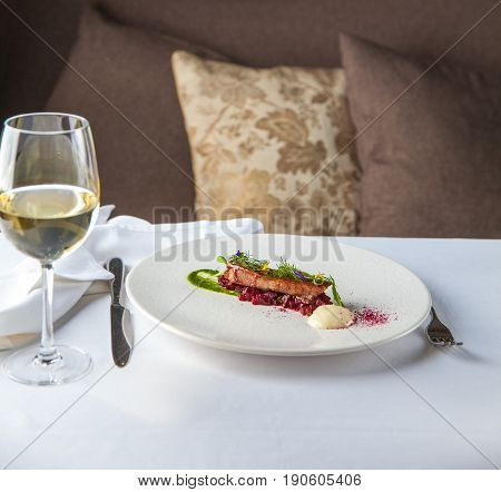 Tuna on a vegetable pillow is served on a white plate in a restaurant. Restaurant food concept.
