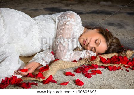 Young beautiful woman in antique lace gown sleeping in a derelict building with rose petals