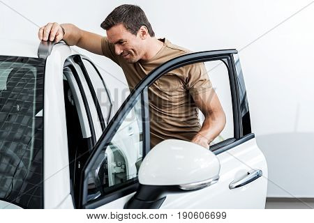 I like this modern design. Side view man expressing cheerfulness while looking at passenger compartment of new automobile. He leaning on roof of it by hands