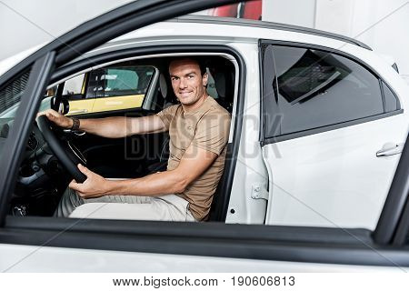 Portrait of man expressing happiness while sitting on comfortable seat of driver in car