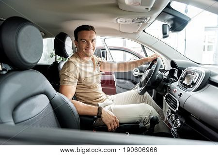 Portrait of male demonstrating gladness while sitting in new vehicle in car dealership