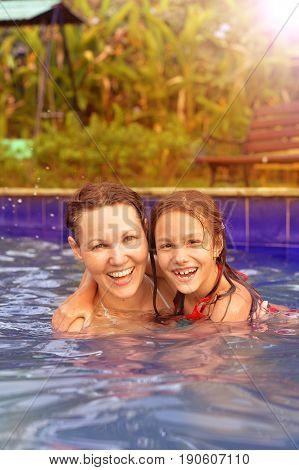 Mother and daughter having fun in swimming pool