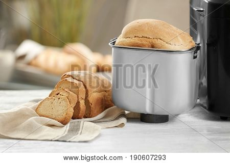 Tasty sliced loaf from bread machine on table