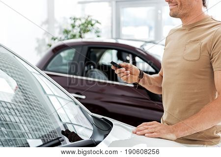 Beaming male keeping digital device in hand while standing near modern vehicle in automobile showroom