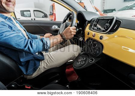 Man showing gladness while is in seat of driver in automobile showroom