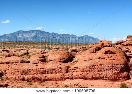 Sugarloaf rock formation in St George Utah, with mountains in the background.