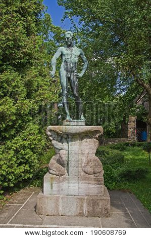 The photo shows an old statue of a naked man. The statue is covered with a patina of green color. It is located on a pedestal made of yellow sandstone. Around the statue grow numerous trees. The statue is located in the area adjacent to Czocha Castle.