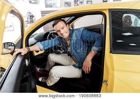 Portrait of man expressing happiness while sitting in vehicle in car dealership. He is opening the door