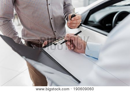 Close up folder with paper. Salesman writing in it. Buyer standing near him in automobile showroom
