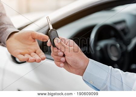 Close up arm of buyer taking automobile clef from agent in automobile showroom