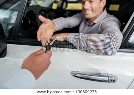 Close up salesman hand giving car key to smiling young client. He sitting in modern car