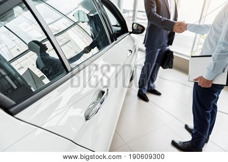 Focus on door of new automobile locating in showroom. Businessman and manager reflecting in window of it and shaking hands
