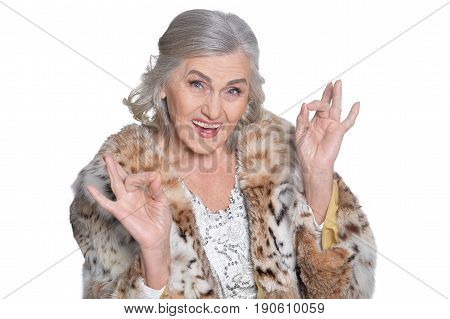 Senior woman in fur shruging the hand on white background