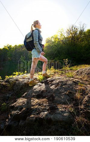 Woman backpacker climbing with backpack in forest on the path during summer. Travel hiking backpacking tourism and people concept