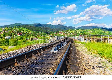 Scenic summer view of the railway track bridge and Carpathian Mountains in Vorokhta, Ivano-Frankivsk Region, Ukraine