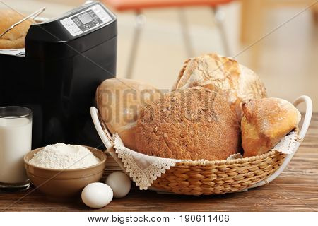 Composition with fresh loaves, bread machine and ingredients on table