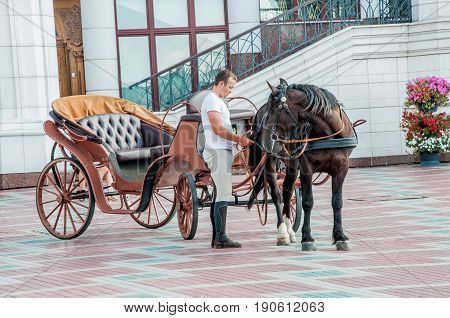 KAZAN RUSSIA - AUGUST 5 2016: A coachman with horse and carriage on the square near the Qol Sharif Mosque