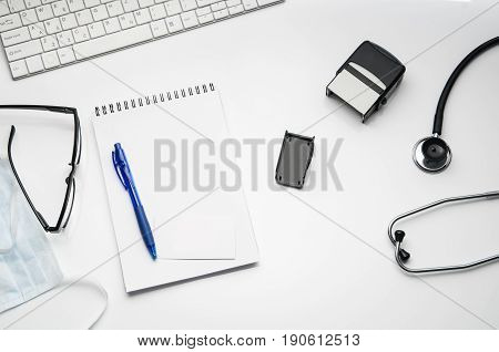 Top view of modern, sterile doctors office desk. Medical accessories isolated on a white table background with copy space around products. Photo taken from above.