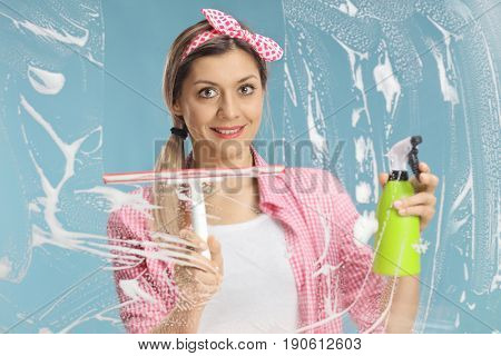 Young woman cleaning glass with a squeegee and a detergent isolated on blue background