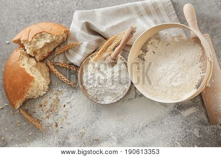 Bowl with flour, sieve and bread chunk on light background