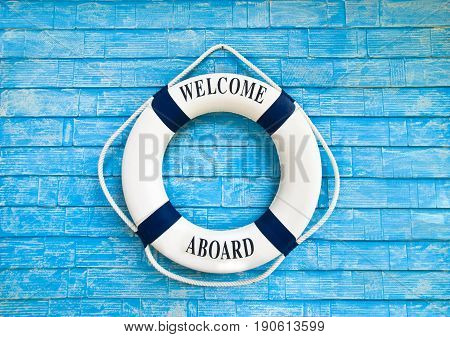 White color Life buoy with welcome aboard on it hanging on blue wall