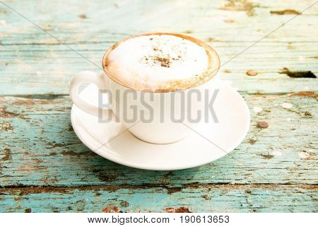 A cup of Cappuccino coffee on grunge blue wood table background give fresh and warm feeling perfect for morning.
