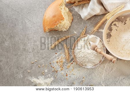 Bowl with flour, sieve and bread chunk on light background, top view
