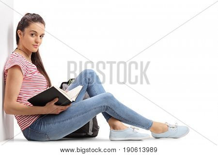 Female teenage student with a book sitting on the floor and leaning against a wall isolated on white background