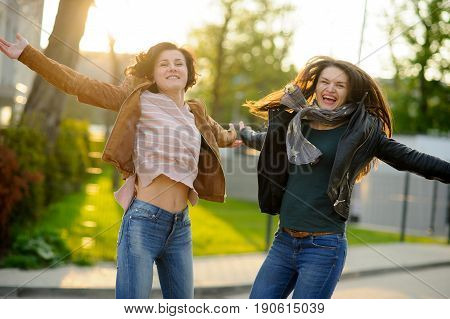 Two cheerful young women. Girlfriends dance. Wonderful spring day. Excellent mood.