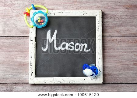 Chalkboard with name MASON on wooden background. Concept of choosing baby name