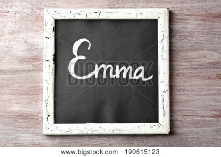 Chalkboard with name EMMA on wooden background. Concept of choosing baby name