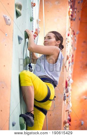 bouldering girl is climbing up the wall