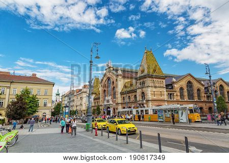 BUDAPEST, HUNGARY - MAY 2017: Central Market Hall in Budapest city, Hungary, Europe. Pedestrian crossing and yellow tram, taxi in foreground, old building and blue sky in background.