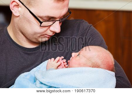 Family fatherhood concept. Daddy holding his little newborn baby in blanket.